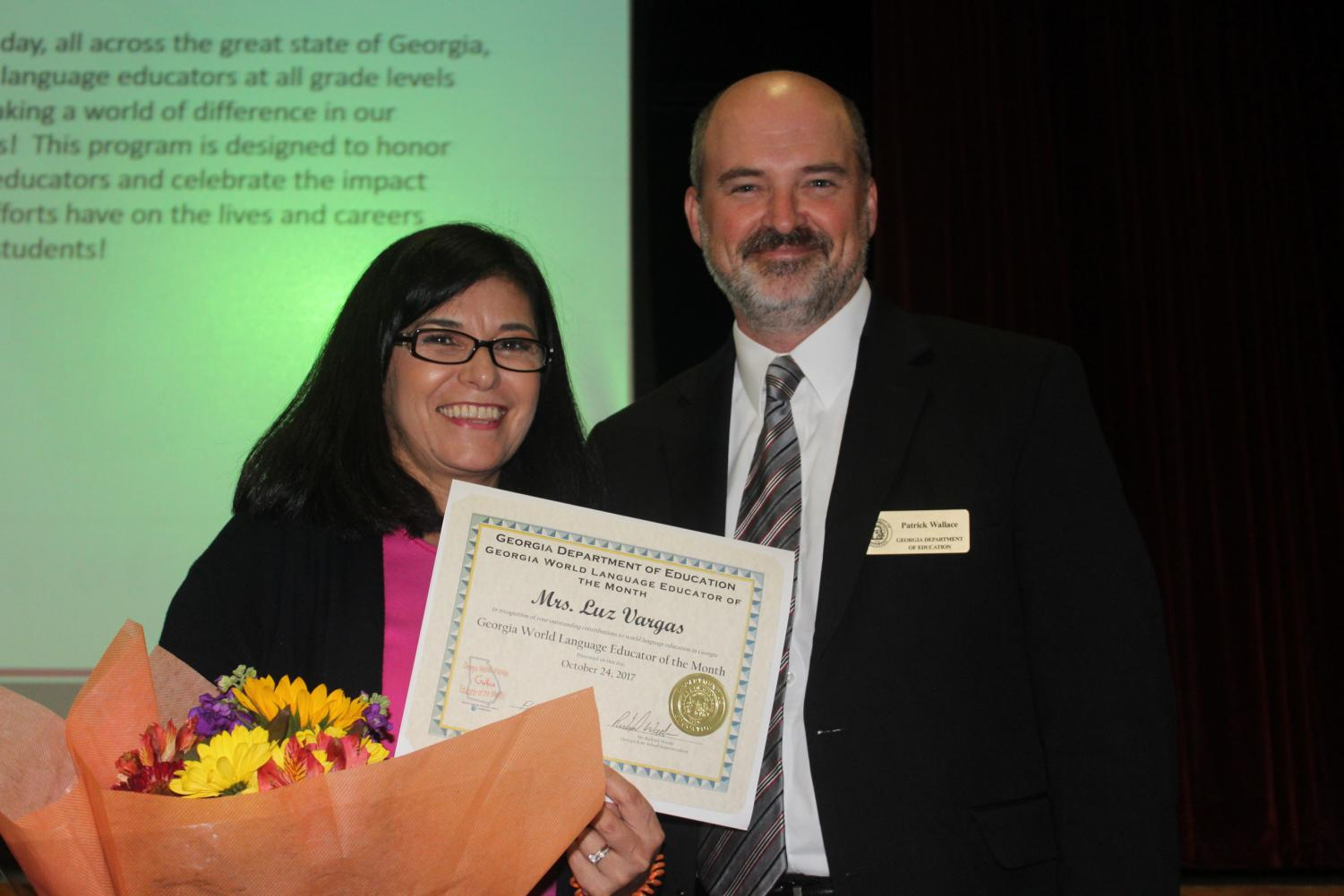 Vargas poses with presenter Patrick Wallace and the World Educator of the month award. This award is presented each month to an educator in the state of Georgia who shows exemplary dedication in the classroom.
