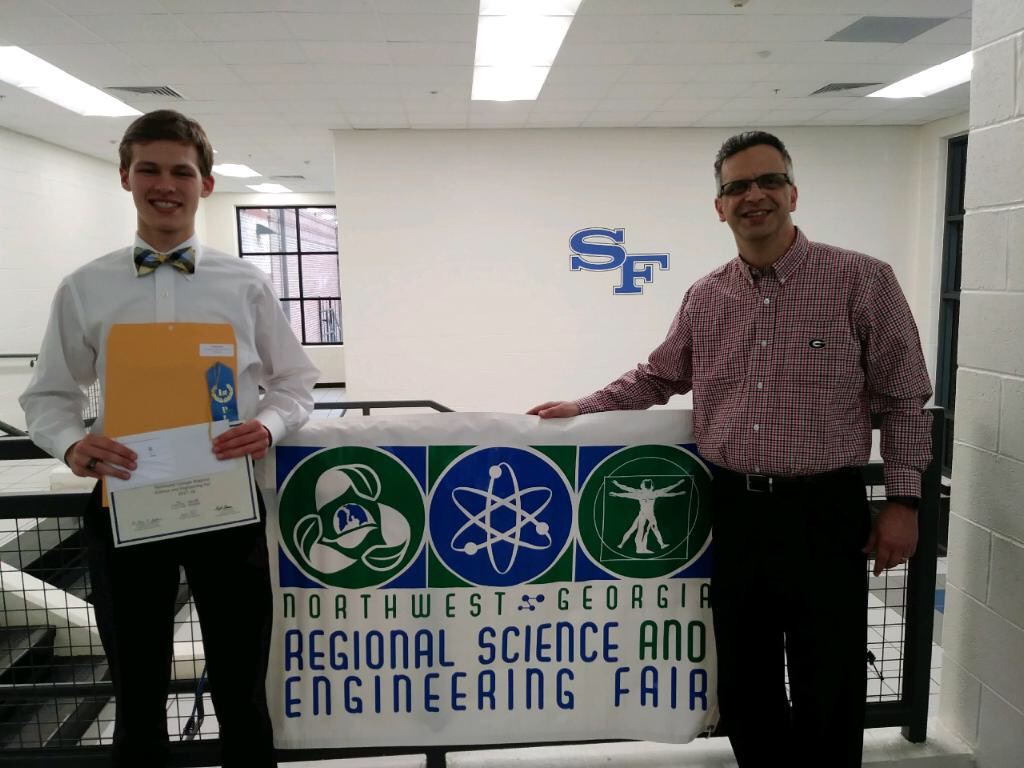 Senior Teddy Campbell stands with his Advanced Placement (AP) chemistry teacher at the Northwest Georgia Regional Science and Engineering Fair. Campbell won first place at this event and will be attending the state fair in March.