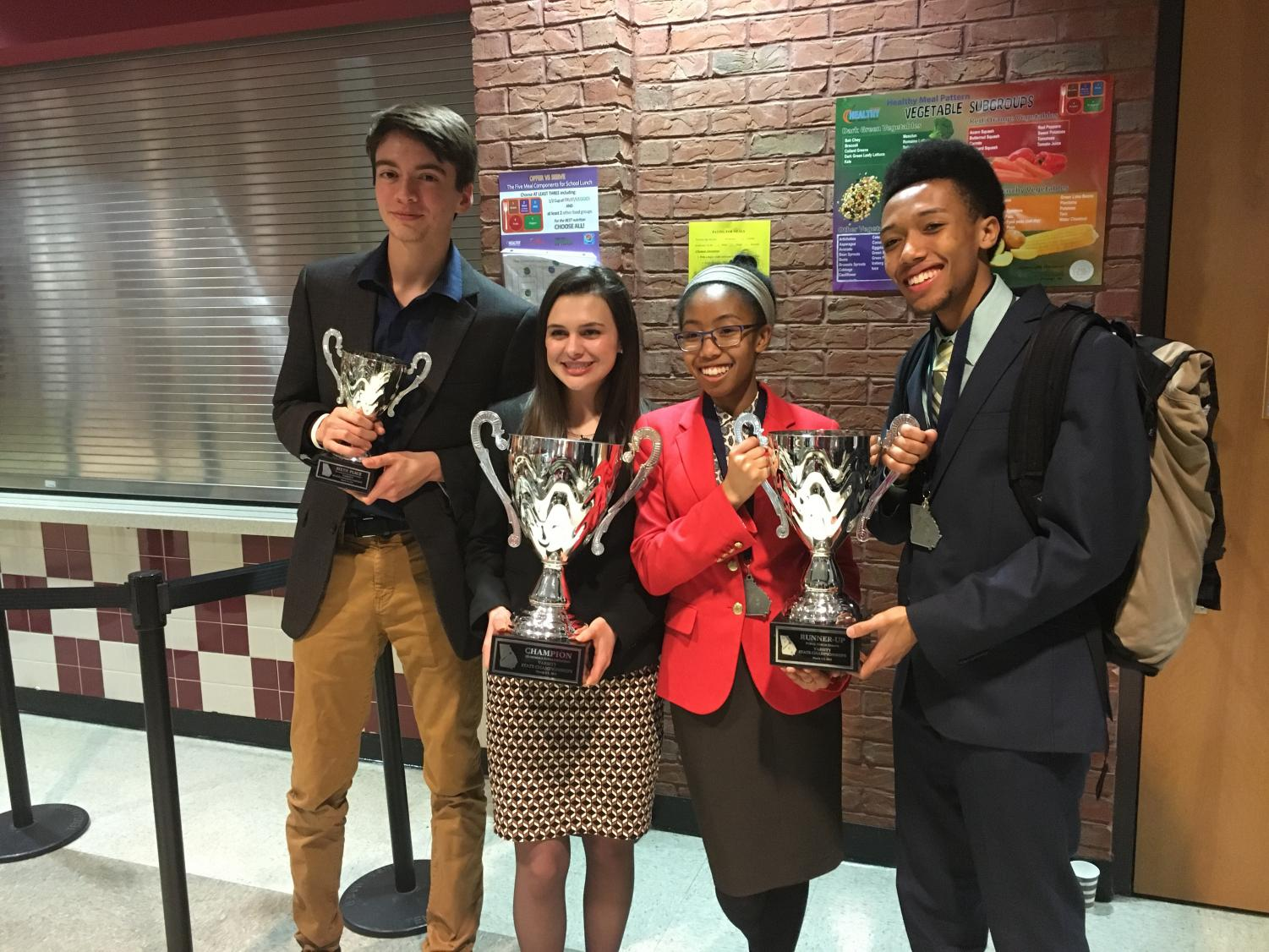 Scott Benefield, Rebekah Carnes, Nyla Crayton, and Caleb Crayton poses with their trophies. Benefield got sixth place and Carnes got first place in the Humorous Interpretation event of speech while the Craytons got second place in the Public Forum.