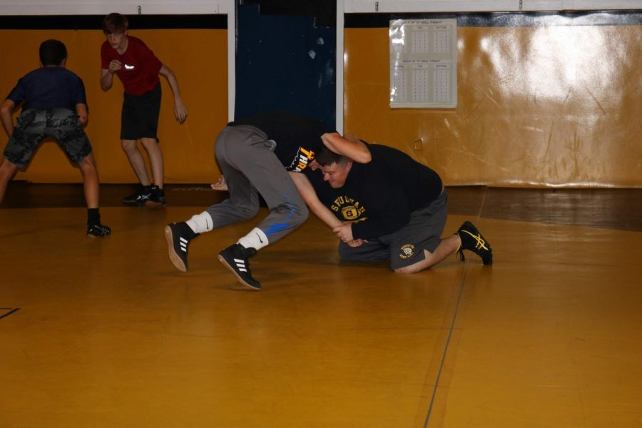Wrestling+coach+James+Patterson+helps+a+player+practice+by+grappling+with+him.+Patterson+has+been+coach+since+he+got+out+of+college.