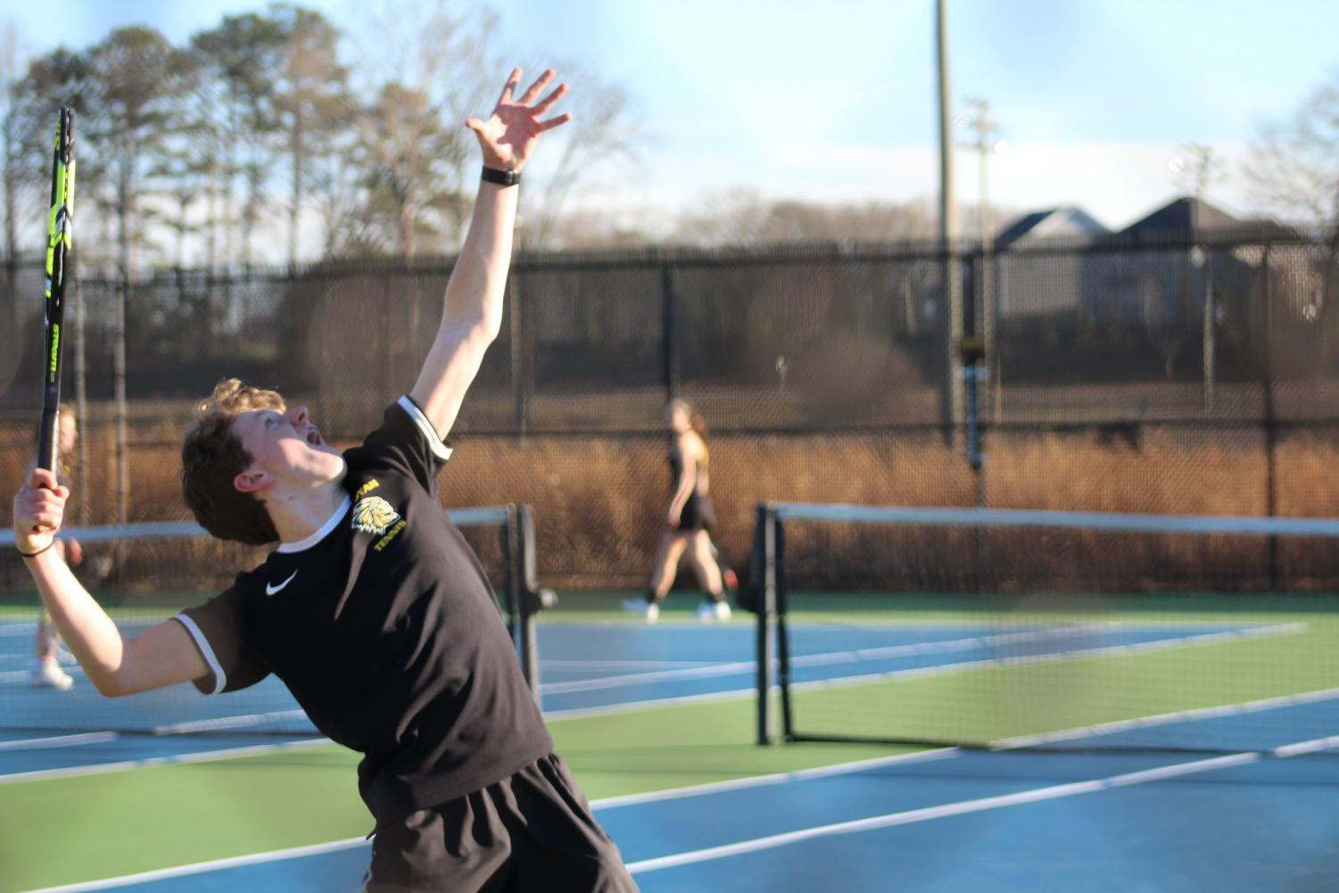 Bailey throws the tennis ball in the air to serve the first round of the match. He made it to State his sophomore year.
