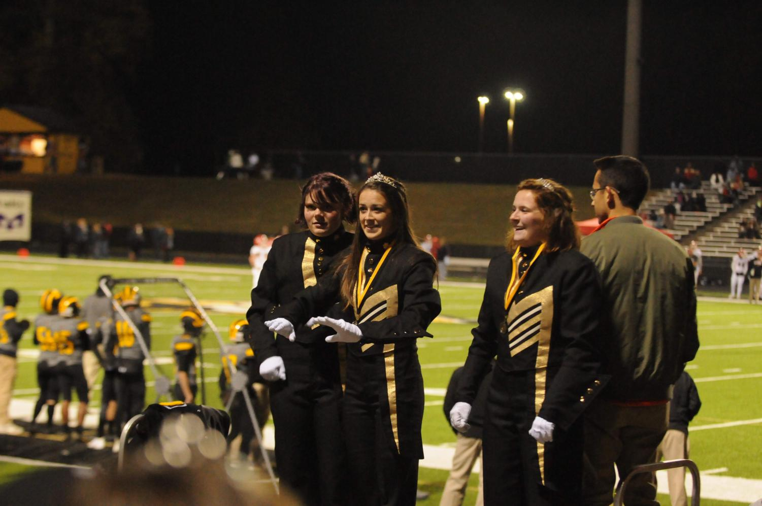Drum majors junior Catie Webb and seniors Cassie Meyers and Madison Joy conduct the band at the final home game of the season against Allatoona High School.  It was the last marching band performance conducted by Myers and Joy.