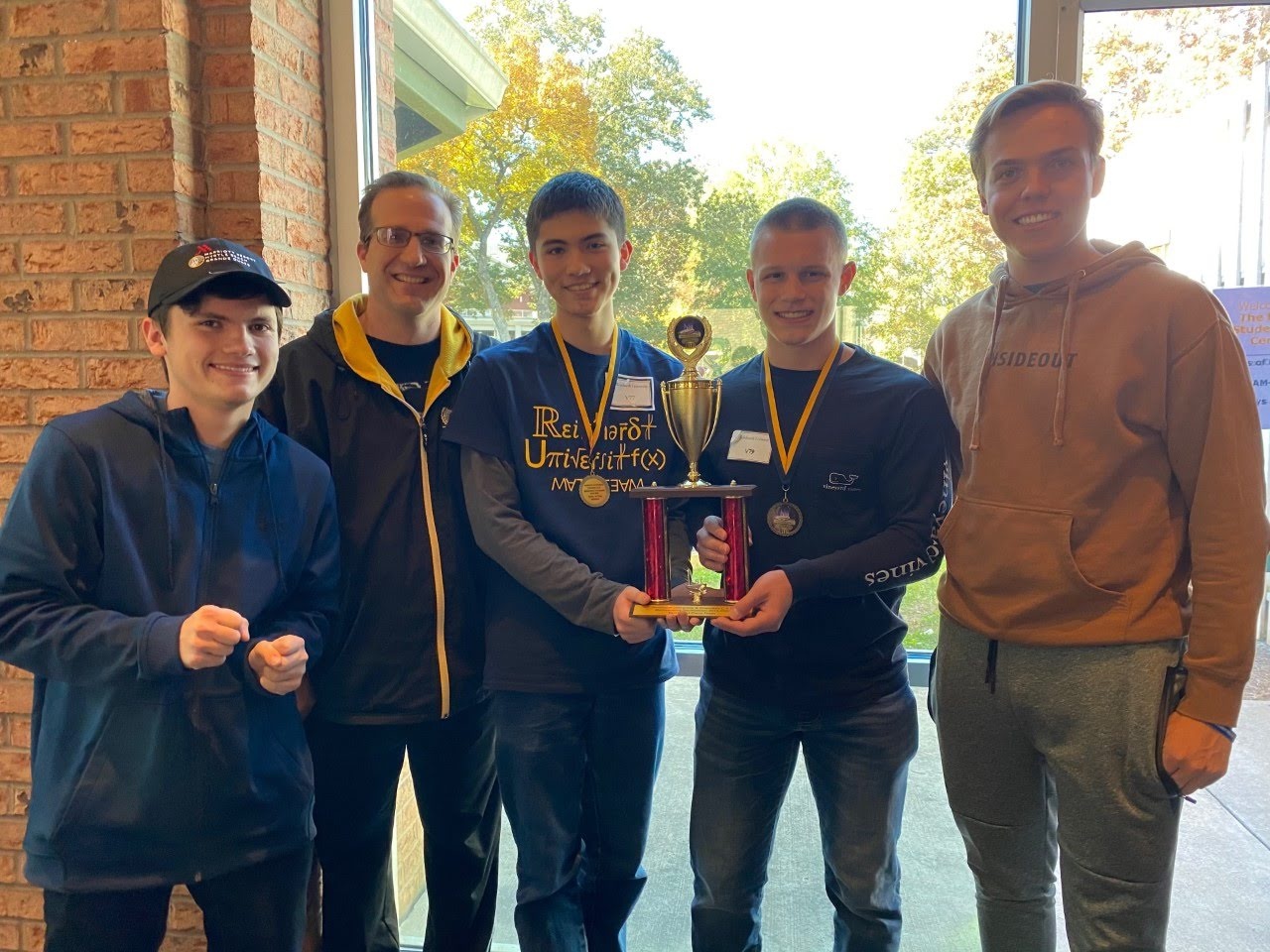 Students from the math team pose alongside Mr. Andy Oberlies after receiving their first-place trophy at the Reinhardt math competition. These students joined Mu Alpha Theta, or Math Honors Society, because of their love for math. Photo provided by Jeremy Jeong