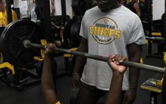 Football players bench press in the weight room. The team gets extra practice in the weight room before Friday night games.