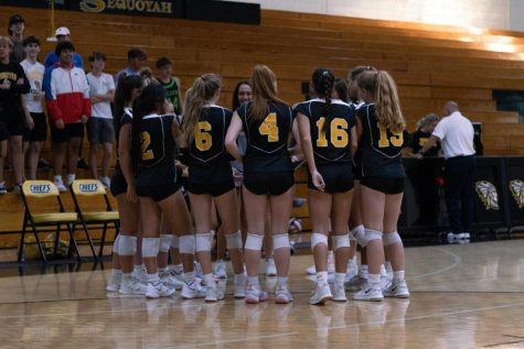 The varsity volleyball team forms a huddle before their second set of the night. The Chiefs swept Chattahoochee 2-0 in their last home game of the regular season.