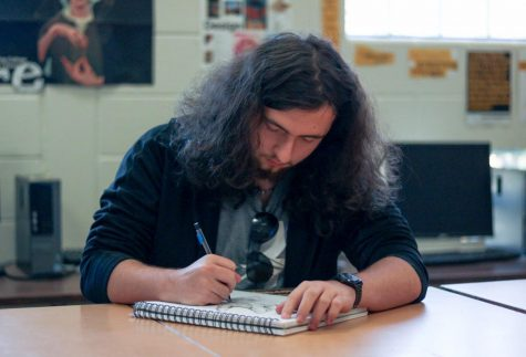 Senior Colin Schell works on a sketch at his desk. Schells biggest art piece took him over 50 hours to complete.
